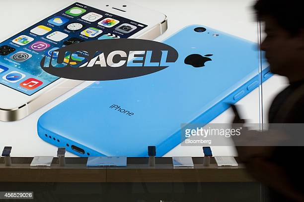 A man walks past an advertisement for Apple Inc iPhones in the window of a Grupo Iusacell SA customer service center in Mexico City Mexico on...