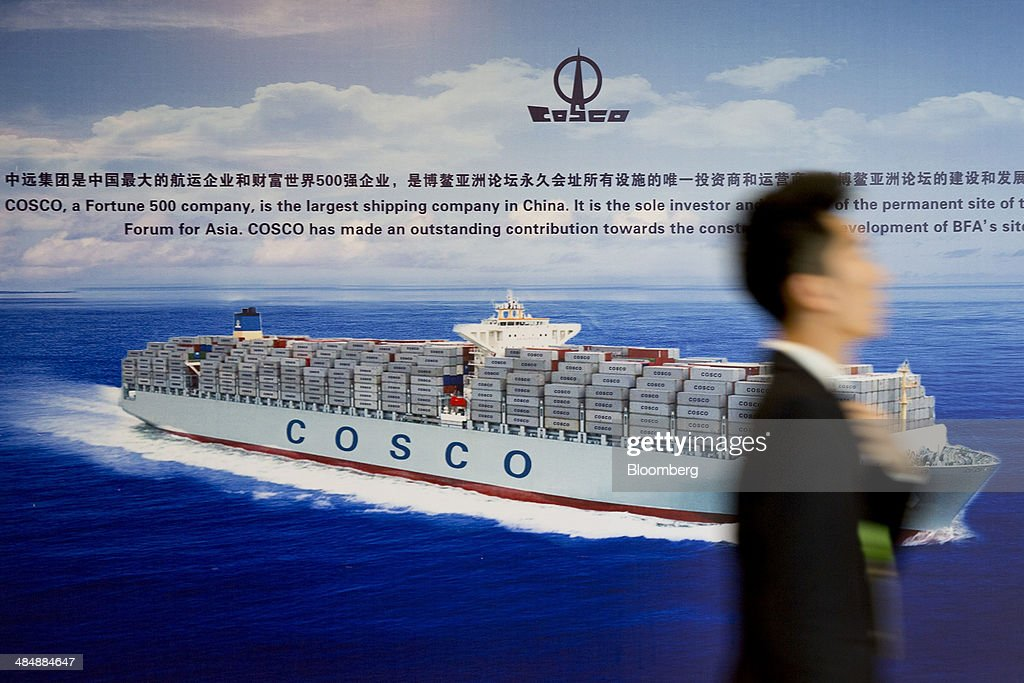 A man walks past an advertisement for China Ocean Shipping Group Co. (Cosco) during the Boao Forum for Asia in Boao, Hainan, China, on Thursday, April 10, 2014. The Boao Forum for Asia takes place from April 8-11. Photographer: Brent Lewin/Bloomberg via Getty Images