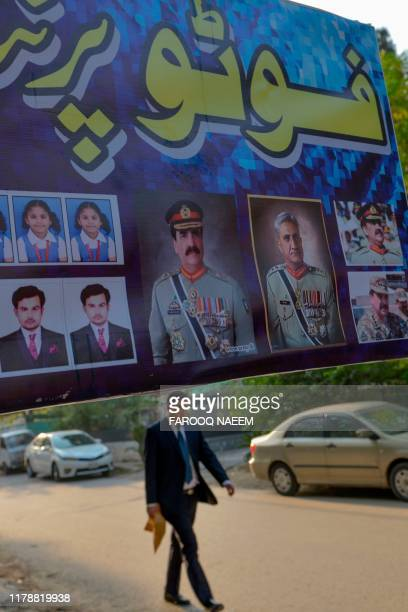 A man walks past an advertisement showing photos of former country army chief Raheel Sharif  and current Army Chief General Qamar Javed Bajwa outside...