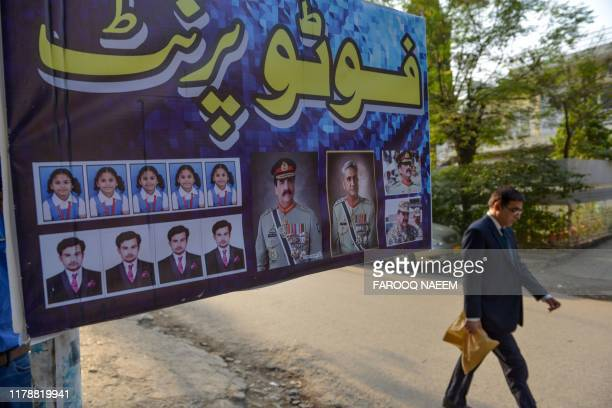 A man walks past an advertisementshowing photos of former countryarmy chiefRaheel Sharif and current Army ChiefGeneralQamar Javed Bajwa outside...