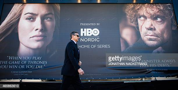 Man walks past an advertising poster to promote the HBO American fantasy drama television series Game of Thrones outside the International Game of...