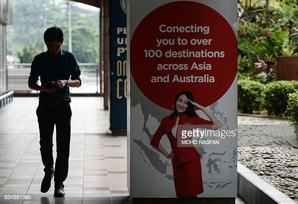 A man walks past an AirAsia advertisement at Kuala Lumpur Sentral railway station in Kuala Lumpur on May 26 2016 Malaysia's Budget carrier AirAsia...
