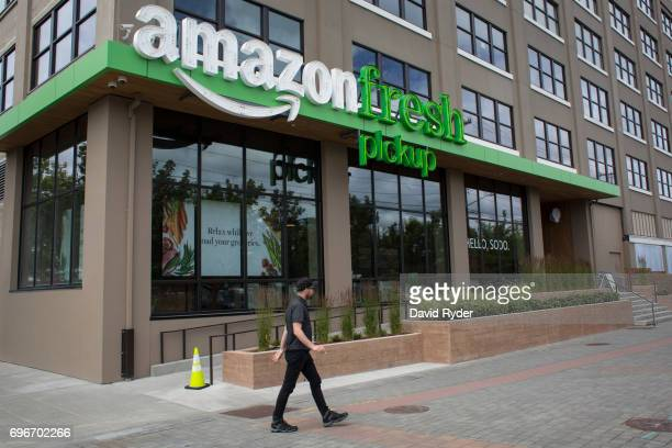 A man walks past an AmazonFresh Pickup location on June 16 2017 in Seattle Washington Amazon announced that it will buy Whole Foods Market Inc for...