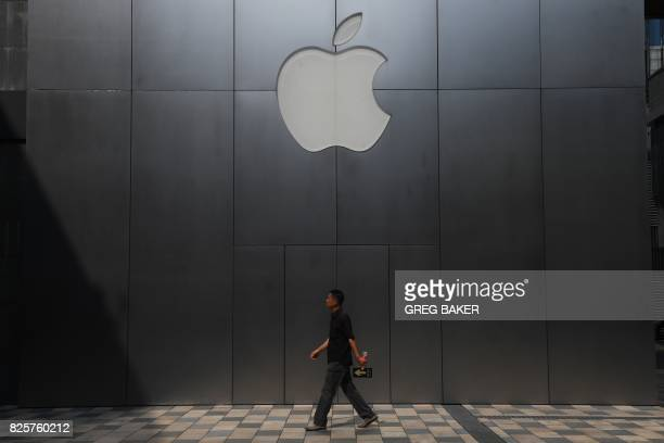 A man walks past an Apple store in Beijing on August 3 2017 Apple has removed software allowing internet users to skirt China's 'Great Firewall' from...