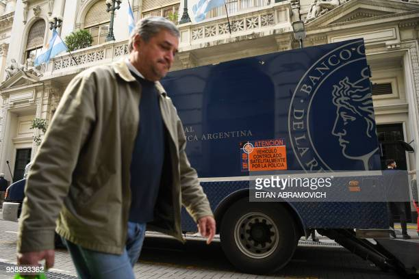 A man walks past an armoured bank truck parked outside Argentina's Cental Bank in downtown Buenos Aires on May 15 2018 Argentina's currency faced a...