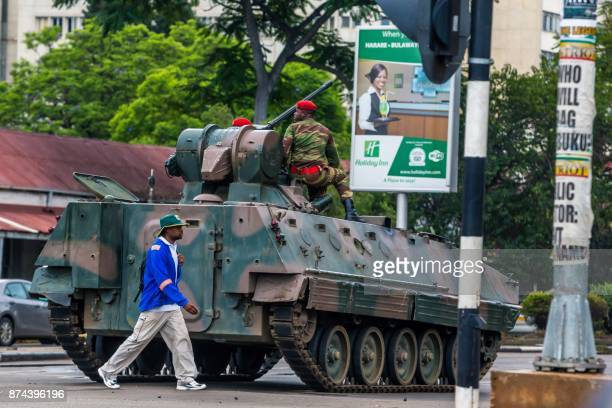 A man walks past an armoured personnel carrier that stations by an intersection as Zimbabwean soldiers regulate traffic in Harare on November 15 2017...