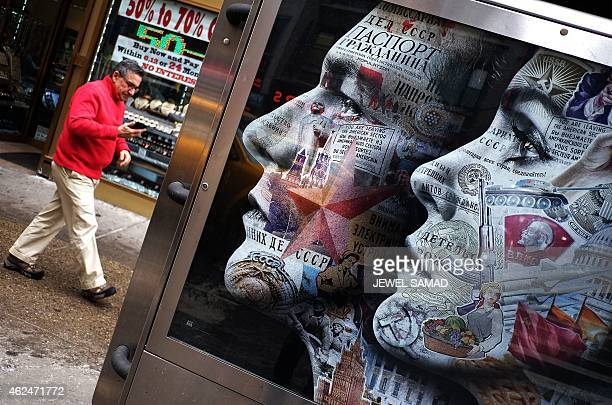 A man walks past an electric billboard advertising television show 'The Americans' in New York's Times Square on January 29 2015 The show a...
