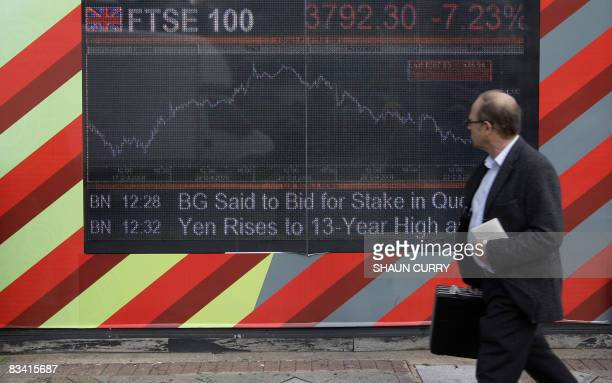A man walks past an electronic display board showing the FTSE 100 share index in London on October 24 2008 Stock markets crashed Friday amid shock at...