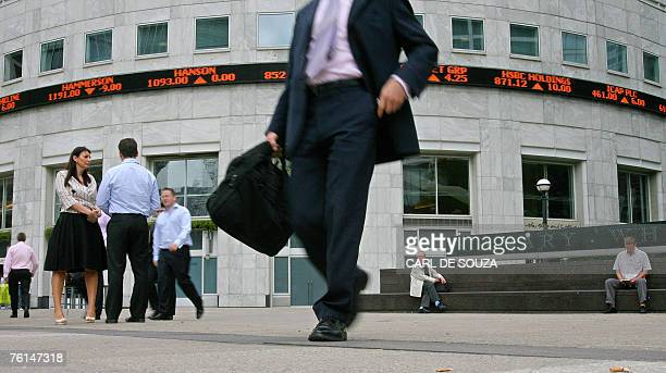 A man walks past an electronic display showing share prices in Canary Wharf business district in east London 17 August 2007 London's FTSE 100 index...
