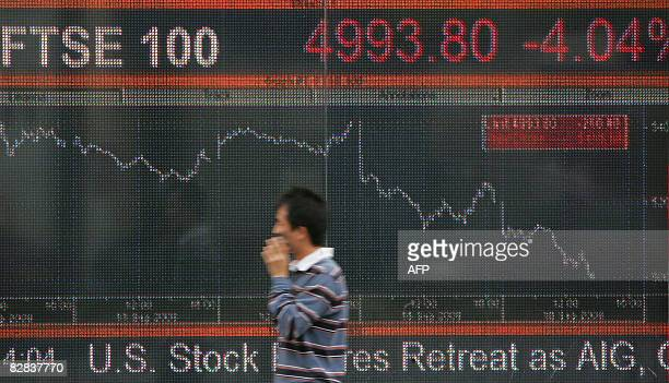 A man walks past an electronic screen in west London which shows the falling FTSE 100 index on September 16 2008 London's FTSE 100 index of leading...