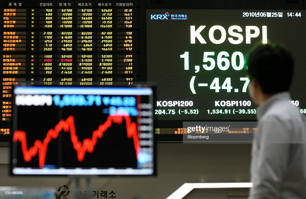 A man walks past an electronic stock board at the Korea Stock Exchange in Seoul, South Korea, on Tuesday, May 25, 2010. Asian stocks and the won plunged to 10-month lows after a report that North Korean leader Kim Jong Il ordered his military to prepare for combat last week. Photographer: SeongJoon Cho/Bloomberg via Getty Images