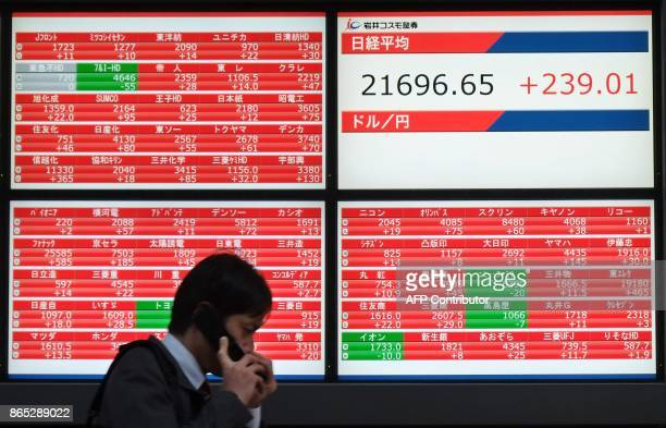 A man walks past an electronics stocks indicator displaying share prices of the Tokyo Stock Exchange in Tokyo on October 23 2017 Tokyo's Nikkei 225...