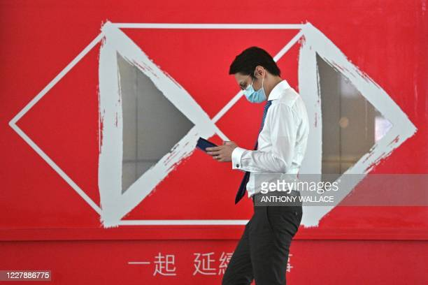 Man walks past an HSBC advert outside a branch of the bank in Hong Kong on August 3, 2020. - HSBC says first half of 2020 profits has plunged 69...