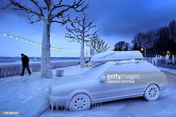 A man walks past an ice covered car on the frozen waterside promenade at Lake Geneva in the city Versoix near Geneva on early February 5 2012 The...