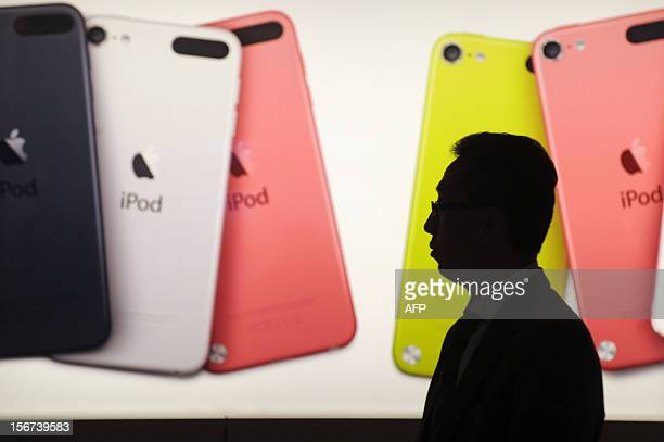 A man walks past an illuminated display outside an Apple store in Hong Kong on November 20 2012 Global sales of 'smart devices' which include...