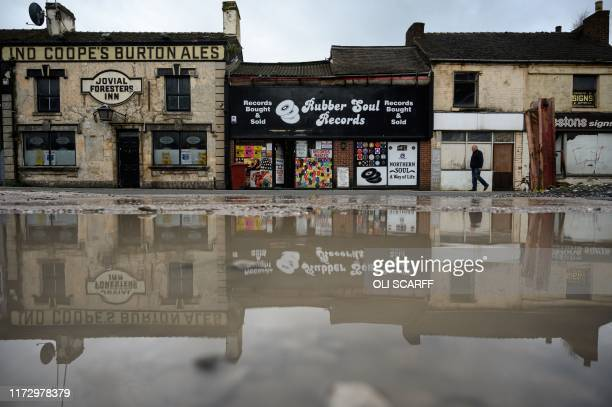A man walks past an independent record shop in the city centre of StokeonTrent northern England on October 1 2019 Brexit is giving us a headache and...