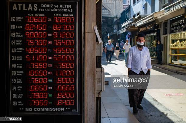 Man walks past an information screen displaying rates in front of an exchange office in Istanbul, on July 29, 2020. - According to reports, the...
