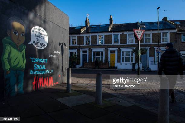 A man walks past artwork by graffiti artist 'The Artful Dodger' on a wall in Brixton in response to an advert by clothing store HM which depicted a...