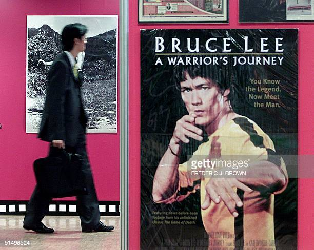 A man walks past artwork of martial arts star Bruce Lee 27 November 2000 at the Dragon Expo 2000 in Hong Kong on the day when the kung fu legend...