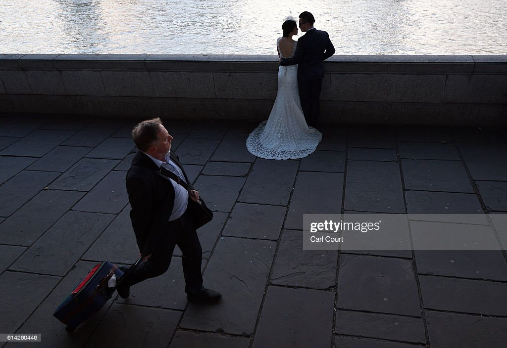 A man walks past as Charles Qian and his fiance Echo Li pose during a pre-wedding photography shoot opposite the Palace of Westminster on October 11, 2016 in London, England. It's a Chinese custom for couples to have their wedding photos taken before they are married and on the wedding day the photos will be shown to guests on cards and big screens. Photography studios such as J.R Studios in east London have seen business boom as the capital has become increasingly popular as a location for pre-wedding photography thanks in part to its instantly recognisable landmarks.