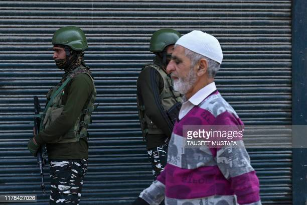 A man walks past as Indian paramilitary troopers stand guard during a lockdown in Srinagar on October 27 2019 Kashmiri separatists observe October 27...
