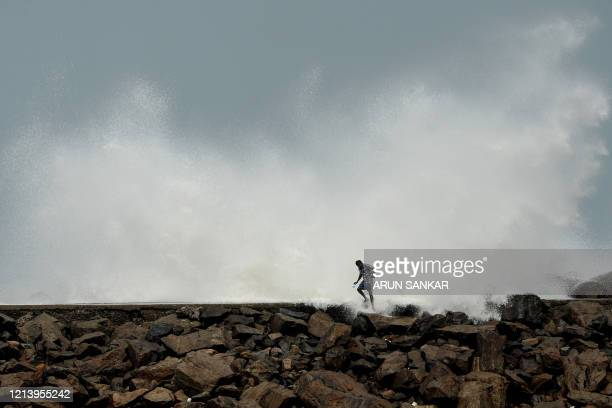 A man walks past as waves hit a breakwater at Kasimedu fishing harbour in Chennai on May 19 as Cyclone Amphan barrels towards India's eastern coast...