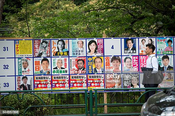 Man walks past at campaign posters with pictures of candidates for the 2016 Upper House election in Tokyo, Japan, on Monday, July 4, 2016. Japanese...
