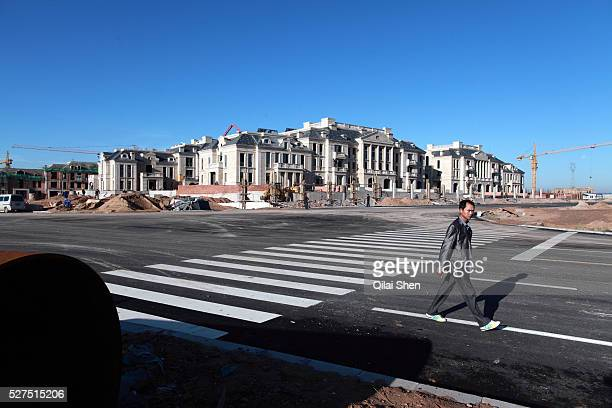 A man walks past at the site of a new luxury housing development being built in the middle of the dessert near the Kangbashi New District of Ordos...