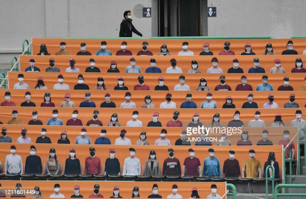 TOPSHOT A man walks past banners depicting spectators in the stands prior to South Korea's new baseball season opening game between SK Wyverns and...