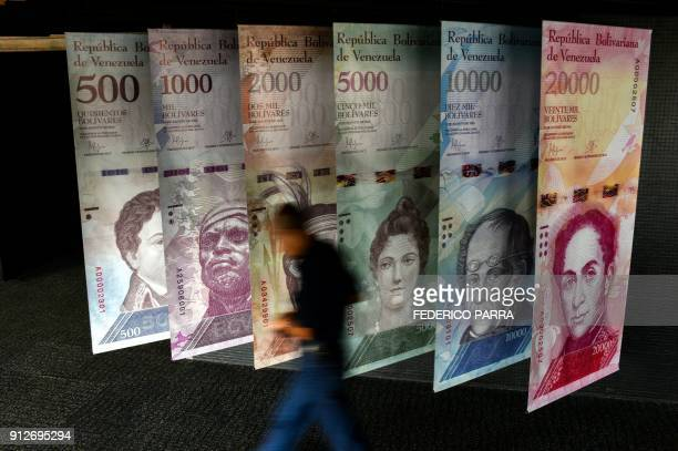 TOPSHOT A man walks past banners showing banners depicting Venezuela's currency the Bolivar at the Central Bank of Venezuela in Caracas on January 31...