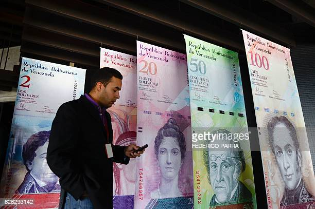 A man walks past banners showing Venezuela's currency the bolivar at the Central Bank of Venezuela in Caracas on December 7 2016 The BCV on Wednesday...