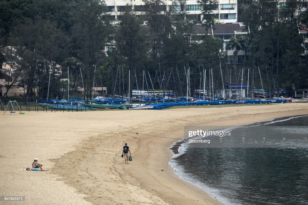 A man walks past beachgoers on Tai Pak beach in Discovery Bay, a residential project developed by Hong Kong Resort Co., on Lantau Island in Hong Kong, China, on Tuesday, March 27, 2018. Private homes in Discovery Bay currently sell from about HK$8 million to HK$80 million, said Denis Ma, head of research for Hong Kong at real-estate services company Jones Lang LaSalle Ltd. Photographer: Justin Chin/Bloomberg via Getty Images