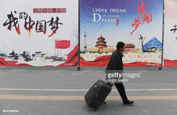 CORRECTION A man walks past billboards promoting the China Dream a slogan associated with Chinese President Xi Jinping in Beijing on April 4 2017 The...