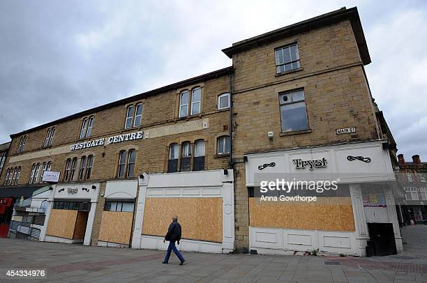 A man walks past boarded up shops on Main Street in the town centre on August 29 2014 in Rotherham England A report released on Tuesday claims at...