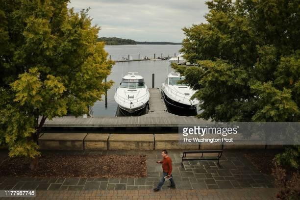 A man walks past boats in the Belmont Bay Harbor Marina