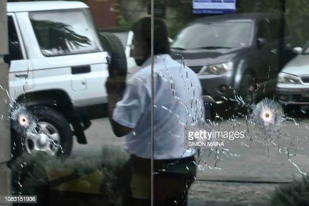 A man walks past bullet marks on a glass outside the DusitD2 hotel complex in Nairobi's Westlands suburb on January 15 in Kenya after a blast...