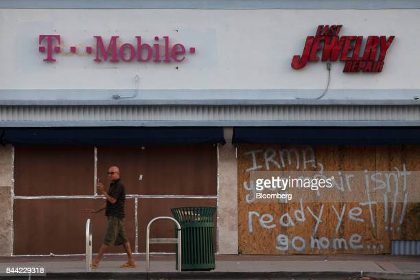 A man walks past businesses boarded up ahead of Hurricane Irma in North Miami Beach Florida US on Friday Sept 8 2017 Hurricane Irma bulked up ahead...
