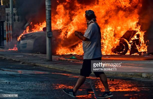 Man walks past cars burning in flames outside the Hotel O'Higgins after being set on fire by demonstrators during a protest against Chilean President...