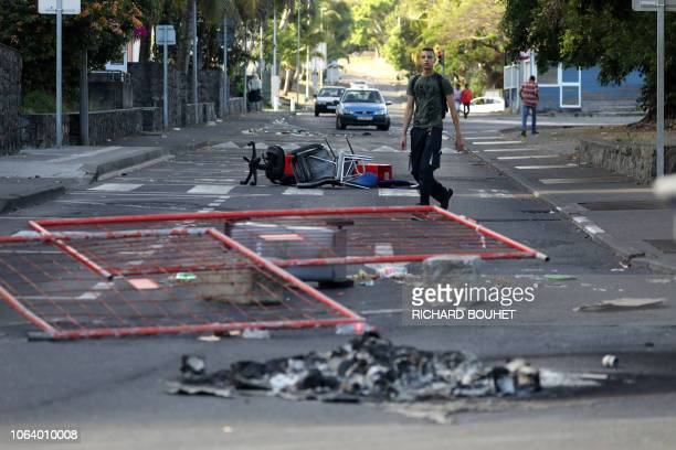 A man walks past charred equipment on the fifth day of protest of the socalled yellow vest movement against high fuel prices in SaintDenisdelaReunion...