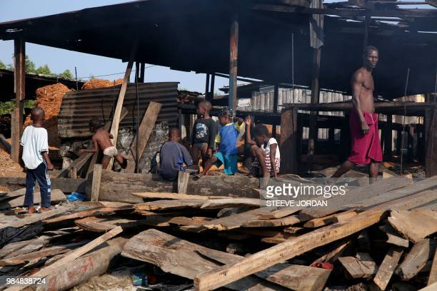 A man walks past children playing in the granve village a fishermen's village outside Libreville on June 21 2018 Foreign fishermen from Nigerians and...