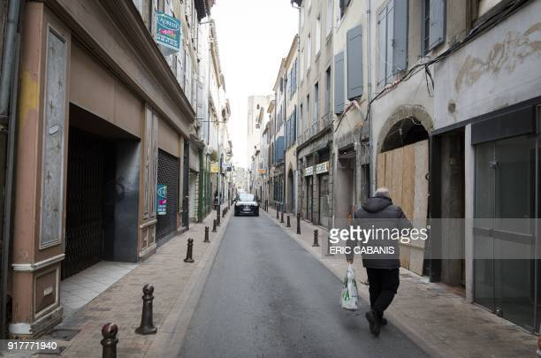 Man walks past closed shops in the city centre of Carcassonne on February 13, 2018. / AFP PHOTO / ERIC CABANIS