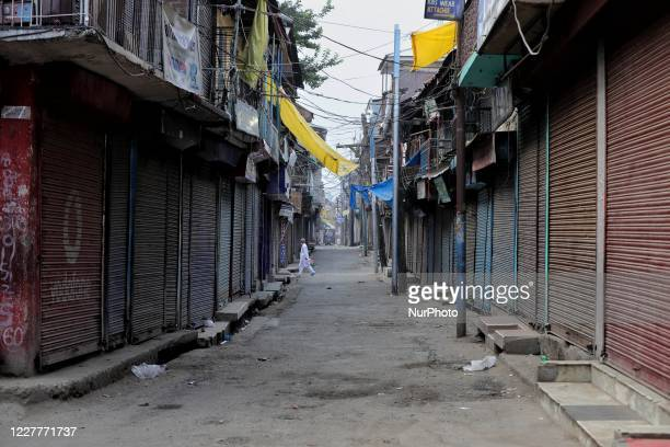 Man walks past Closed Shutters early morning in Sopore Town of District Baramulla, Jammu and Kashmir, India amid COVID-19 Lockdown due to spike in...