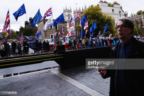 A man walks past collected pro and antiBrexit flags and banners on Abingdon Street outside the Houses of Parliament in London England on October 21...