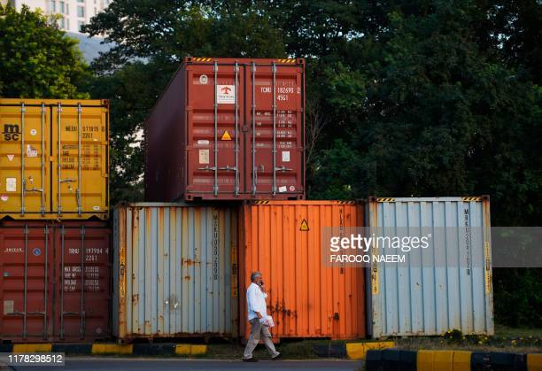 A man walks past containers placed on a roadside in Islamabad on October 26 ahead of opposition party Jamiat UlemaeIslam antigovernment protest ...