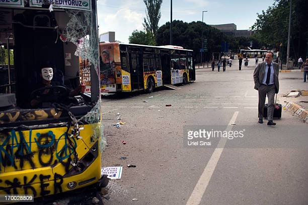 A man walks past damaged buses near Taksim Square on June 6 2013 in Istanbul Turkey The protests began initially over the fate of Taksim Gezi Park...
