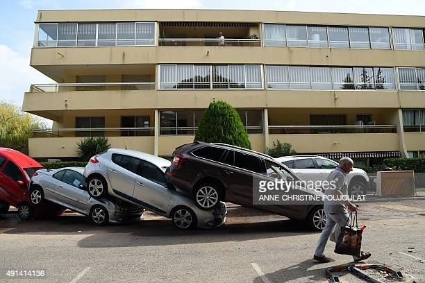 A man walks past damaged cars in MandelieulaNapoule southern France on October 5 2015 after floods tore through the French Riviera leaving 18 dead...