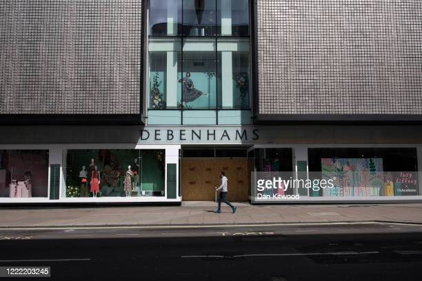Man walks past Debenhams department store on Oxford Street as shops and businesses remain closed on May 01, 2020 in London, England. British Prime...