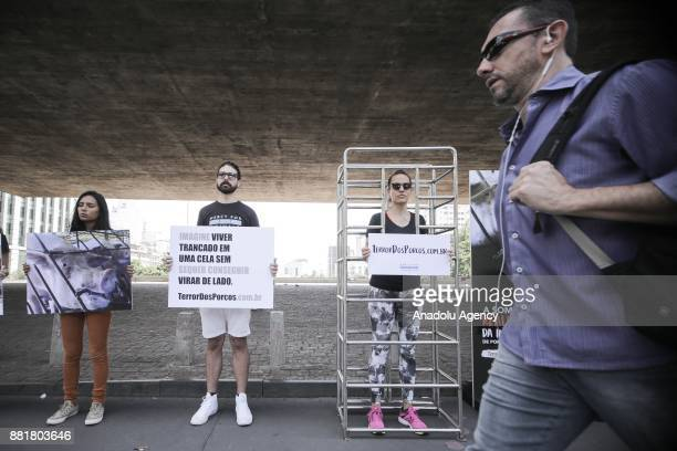 A man walks past demonstrators as they hold banners during a demonstration organized by the International NGO Mercy For Animals to draw attention of...