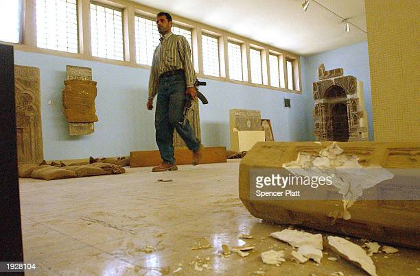 A man walks past destroyed art while guarding the Iraqi National Museum April 13 2003 in Baghdad Iraq The museum was destroyed in the days after...