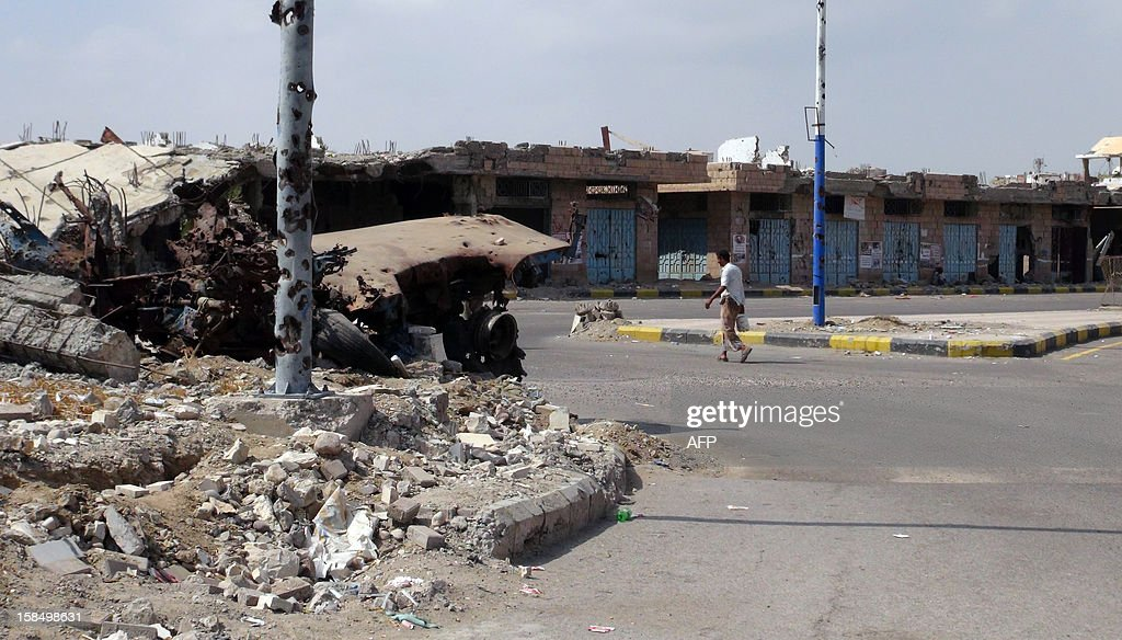 A man walks past destroyed buildings in Zinjibar, capital of Abyan province in southern Yemen on December 5, 2012, six months after the Yemeni army ousted al-Qaeda loyalists from the region. Before a counter-offensive by the army earlier this year, Al-Qaeda held large swathes of southern Yemen. But since its loss of a string of towns near the port city of Aden in June, most have fled into desert regions farther east. Although weakened, they continue to launch hit-and-run attacks on government and civilian targets across Yemen.